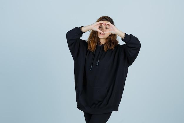 Jovem senhora com um capuz enorme, calças mostrando um gesto de coração e uma aparência bonita, vista frontal