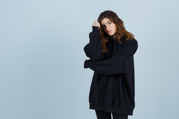 Jovem senhora com um capuz enorme, calças posando em pé e com uma aparência atraente, vista frontal.