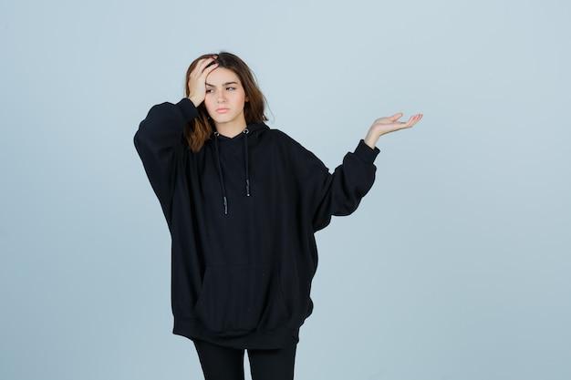 Jovem senhora com um capuz enorme, calças segurando a mão na cabeça enquanto mostra algo e parece esquecido, vista frontal.