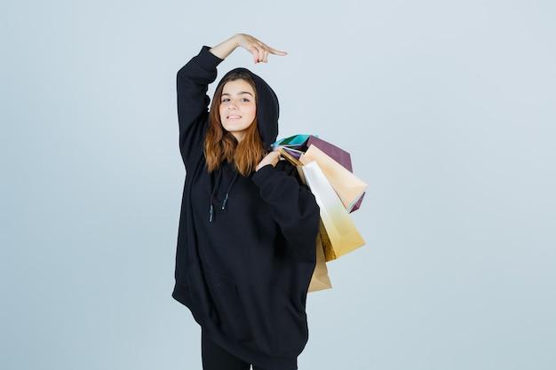 Jovem senhora com um capuz enorme, calças segurando pacotes no ombro enquanto aponta para o lado direito e está linda, vista frontal.