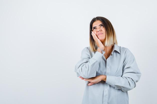 Jovem senhora com uma camisa enorme, segurando a mão na bochecha enquanto olha para cima e parece pensativa, vista frontal.