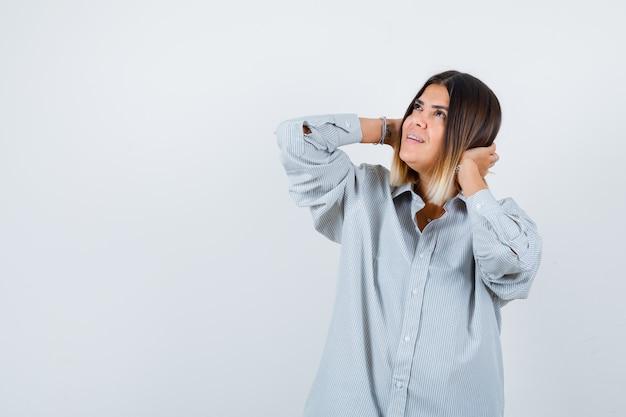 Jovem senhora com uma camisa grande, segurando as mãos atrás da cabeça e olhando cuidadosa, vista frontal.