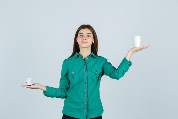 Jovem senhora com uma camisa, segurando copos plásticos de café e parecendo satisfeita, vista frontal.