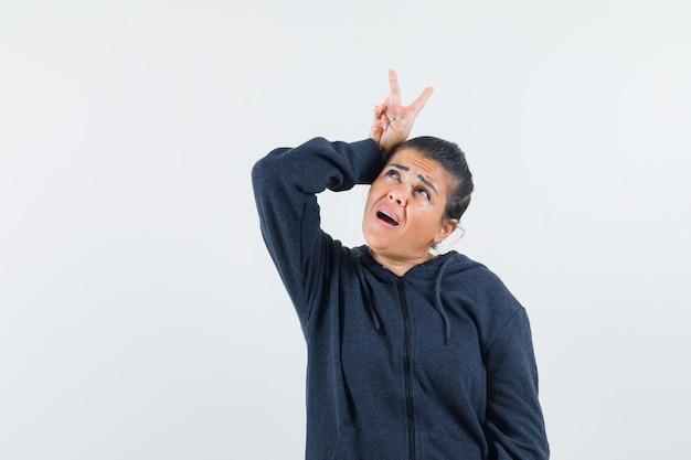 Jovem senhora com uma jaqueta mostrando o sinal de v na cabeça enquanto olha para cima e parece estranha