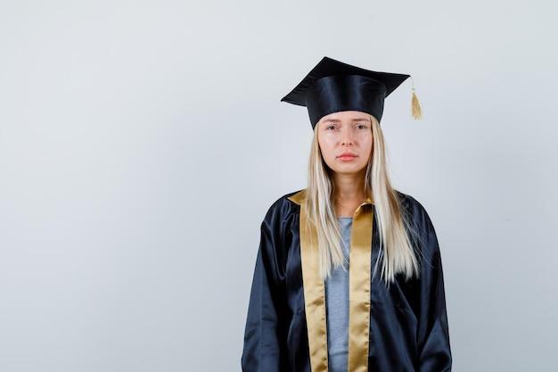 Jovem senhora com vestido acadêmico, olhando para a câmera e parecendo melancólica