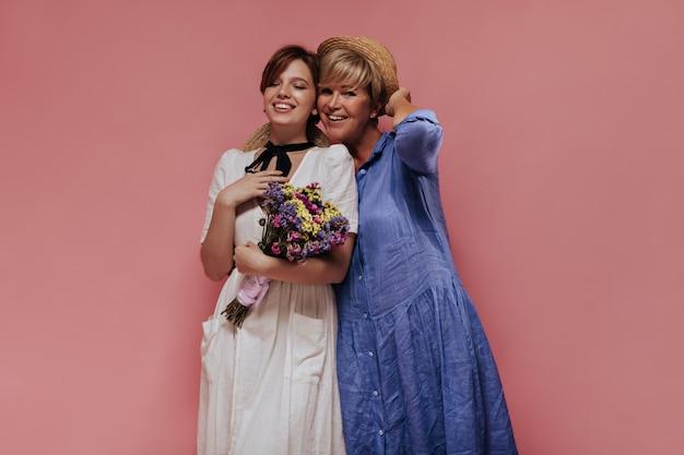 Jovem senhora com vestido leve, sorrindo, segurando flores silvestres e posando com uma mulher alegre com chapéu de palha e roupa jeans em fundo rosa.