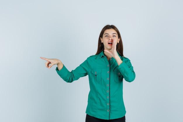 Jovem senhora contando o segredo por trás da mão enquanto aponta de lado com uma camisa verde e parece preocupada. vista frontal.