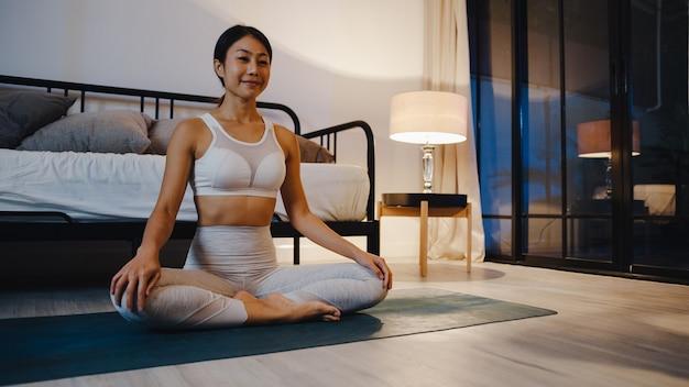 Jovem senhora da ásia em roupas esportivas, fazendo exercícios de ioga malhando na sala de estar em casa à noite.