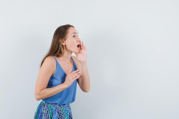 Jovem senhora de blusa azul, saia chamando alguém em voz alta e olhando cuidadosa, vista frontal.