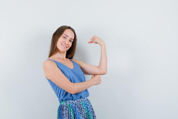 Jovem senhora de blusa azul, saia mostrando os músculos e parecendo autoconfiante, vista frontal.