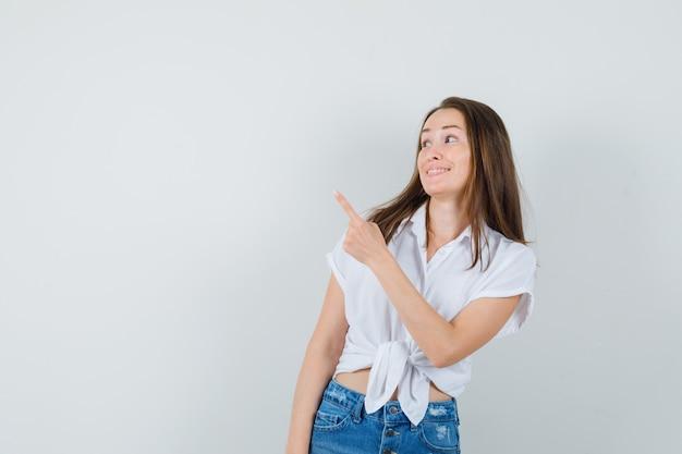 Jovem senhora de blusa branca, apontando para trás e olhando jojoyus, vista frontal. espaço para texto