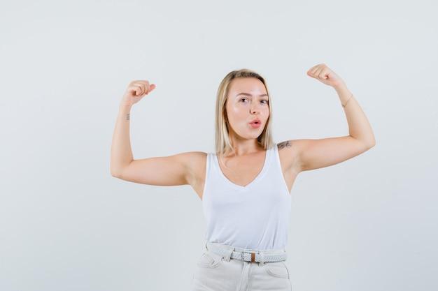 Jovem senhora de blusa branca levantando os braços, mostrando os músculos e parecendo poderosa