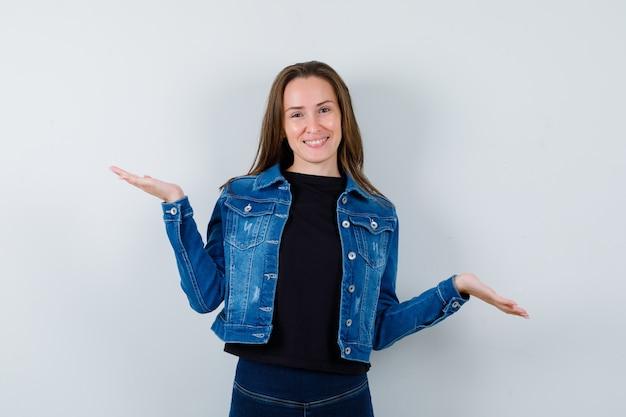Jovem senhora de blusa fazendo gesto de escalas e olhando confiante, vista frontal.