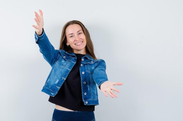 Jovem senhora de blusa, jaqueta abrindo os braços para um abraço e olhando alegre, vista frontal.