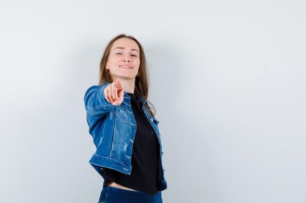 Jovem senhora de blusa, jaqueta, apontando para a câmera e olhando confiante, vista frontal.