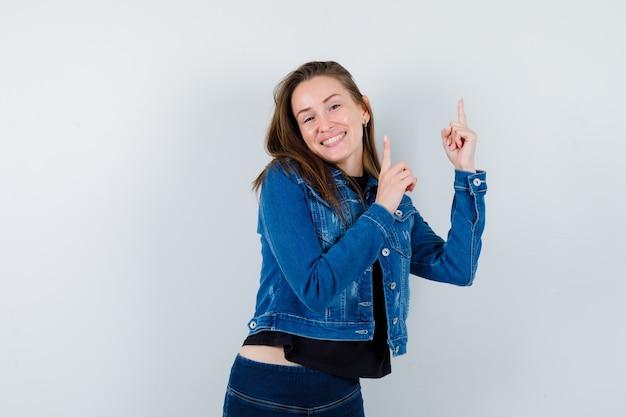Jovem senhora de blusa, jaqueta apontando para cima e olhando alegre, vista frontal.