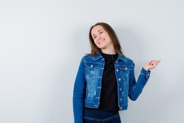 Jovem senhora de blusa, jaqueta apontando para o lado e olhando alegre, vista frontal.