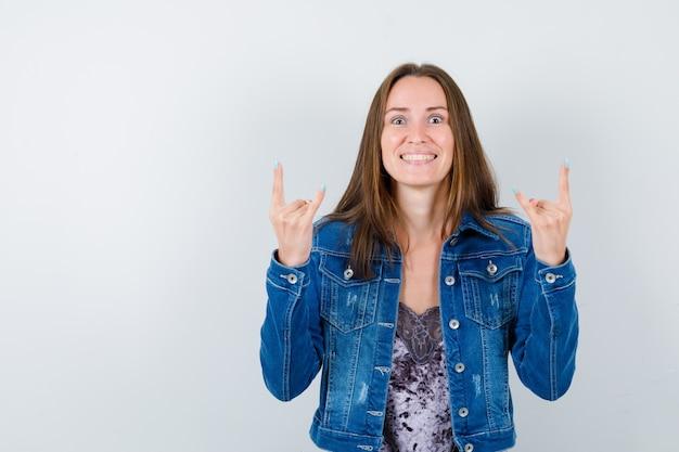 Jovem senhora de blusa, jaqueta jeans, fazendo o símbolo do rock e parecendo louca, vista frontal.