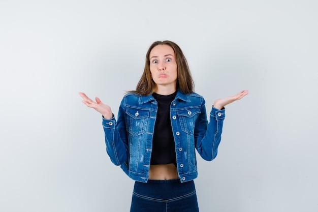 Jovem senhora de blusa, jaqueta, jeans, mostrando um gesto de impotência e parecendo confusa, vista frontal.