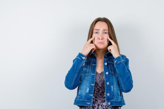 Jovem senhora de blusa, jaqueta jeans, segurando os dedos nas bochechas enquanto chora e parece ofendida, vista frontal.