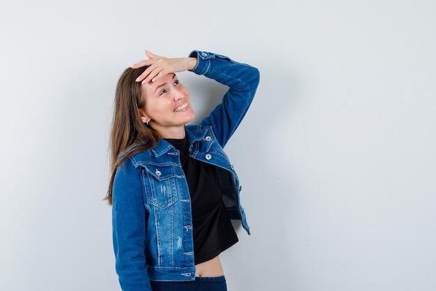 Jovem senhora de blusa, jaqueta, segurando a mão na testa enquanto posava e parecia um sonho, vista frontal.