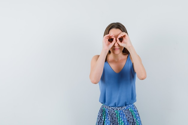 Jovem senhora de blusa, saia mostrando gesto binocular e olhando concentrada, vista frontal. espaço para texto