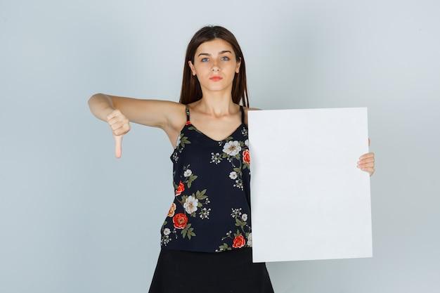 Jovem senhora de blusa, saia segurando uma tela em branco, mostrando o polegar para baixo e parecendo descontente, vista frontal.