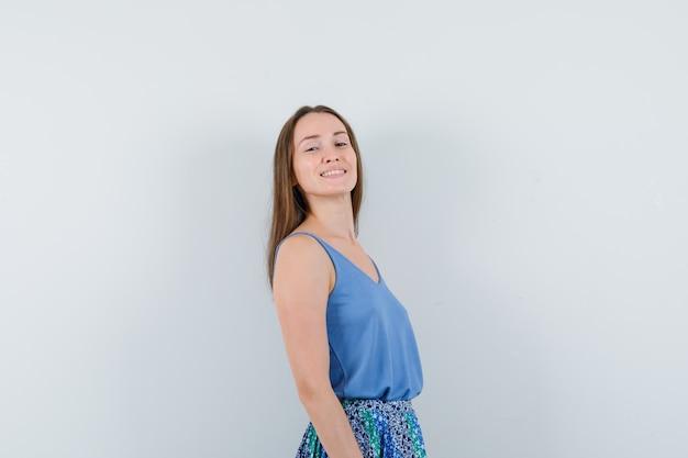 Jovem senhora de blusa, saia sorrindo e olhando otimista, vista frontal.