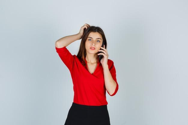 Jovem senhora de blusa vermelha, saia falando no celular