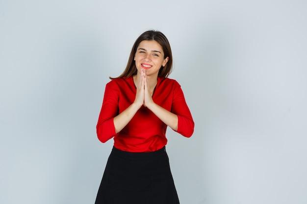 Jovem senhora de blusa vermelha, saia mostrando gesto namastê e parecendo tranquila