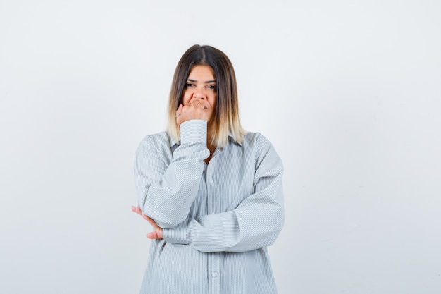 Jovem senhora de camisa grande, roendo as unhas e parecendo pensativa, vista frontal.