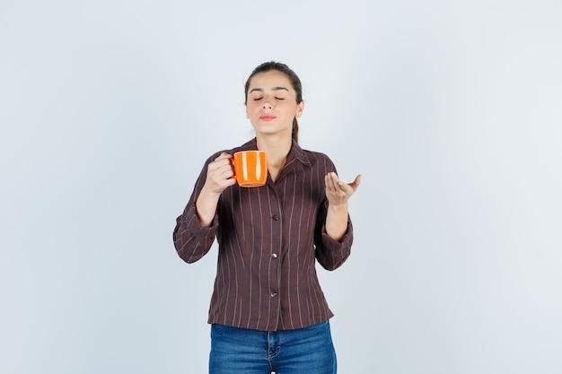 Jovem senhora de camisa, jeans, cheirando o aroma de chá e parecendo satisfeita, vista frontal.
