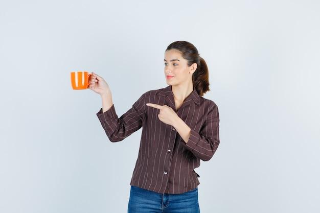 Jovem senhora de camisa, jeans mostrando a xícara, apontando para o lado e parecendo satisfeita, vista frontal.
