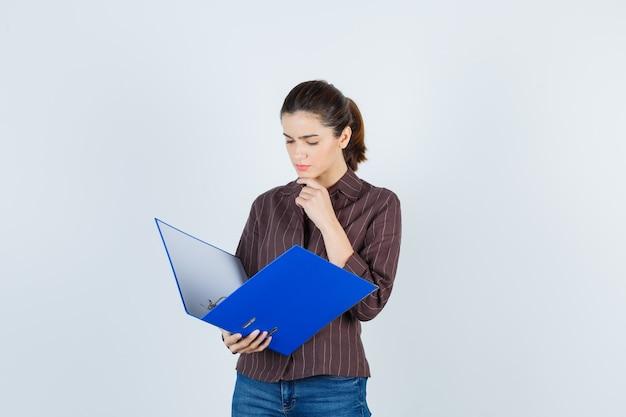 Jovem senhora de camisa, jeans, olhando na pasta, com a mão no queixo e parecendo perplexa, vista frontal.