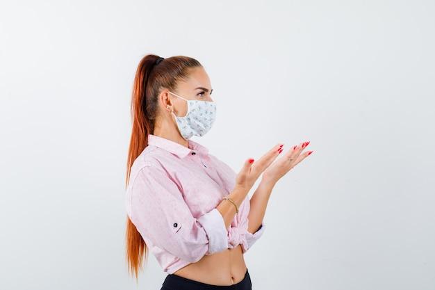 Jovem senhora de camisa, máscara fingindo mostrar algo e parecendo espantada, vista frontal.