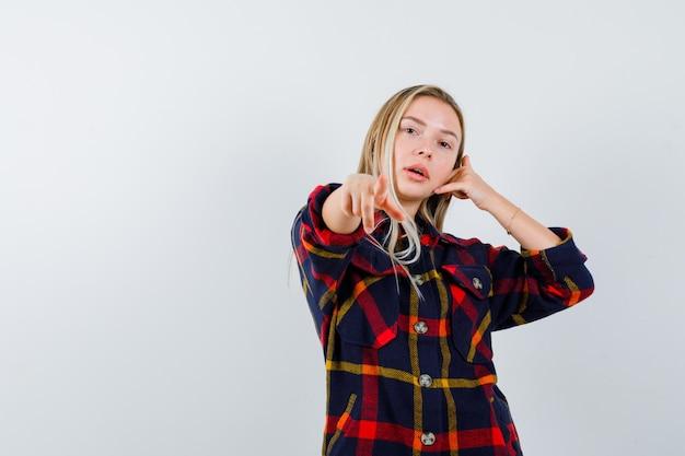 Jovem senhora de camisa quadrada, apontando para a câmera, segurando a mão na cabeça e olhando confiante, vista frontal.