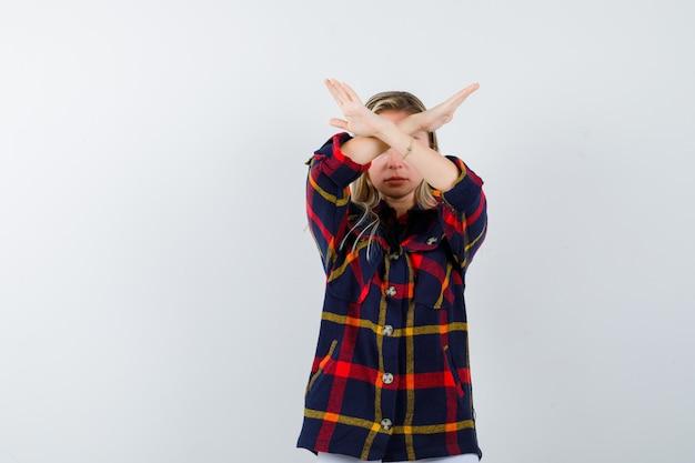 Jovem senhora de camisa quadrada, mostrando o gesto de parar e olhando séria, vista frontal.
