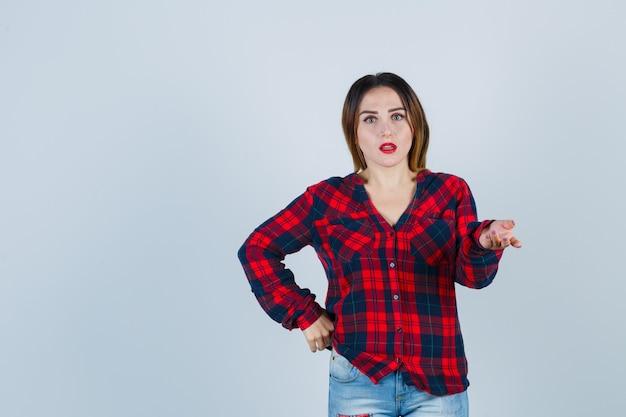 Jovem senhora de camisa quadrada, mostrando o gesto de pergunta e olhando perplexa, vista frontal.
