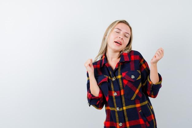 Jovem senhora de camisa quadrada, mostrando o gesto do vencedor e parecendo com sorte, vista frontal.