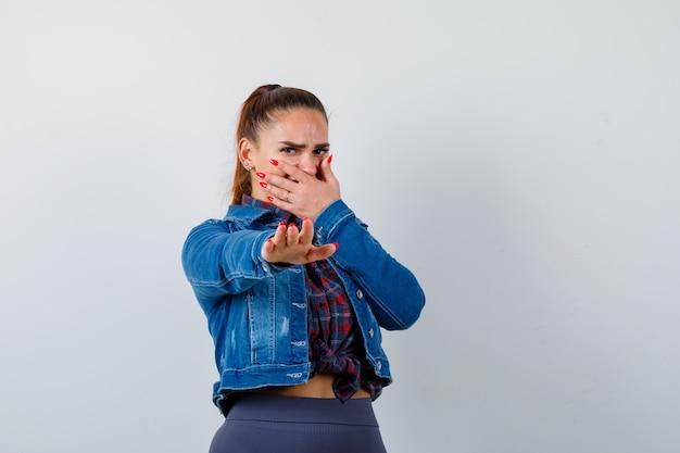 Jovem senhora de camisa quadriculada, jaqueta jeans com a mão na boca enquanto mostra o gesto de pare e parece enojada, vista frontal.