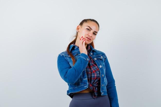 Jovem senhora de camisa quadriculada, jaqueta jeans com a mão no queixo e parecendo confiante, vista frontal.