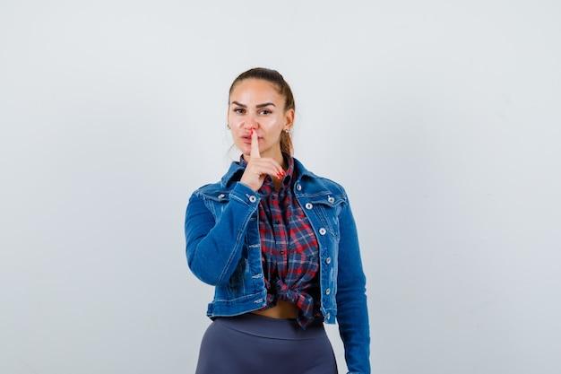 Jovem senhora de camisa quadriculada, jaqueta jeans, mostrando o gesto de silêncio e olhando cuidadosa, vista frontal.