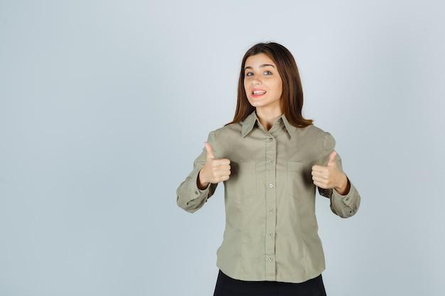 Jovem senhora de camisa, saia mostrando dois polegares para cima e parecendo feliz, vista frontal.