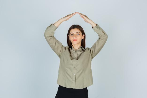 Jovem senhora de camisa, saia mostrando gesto do telhado da casa e parecendo satisfeita