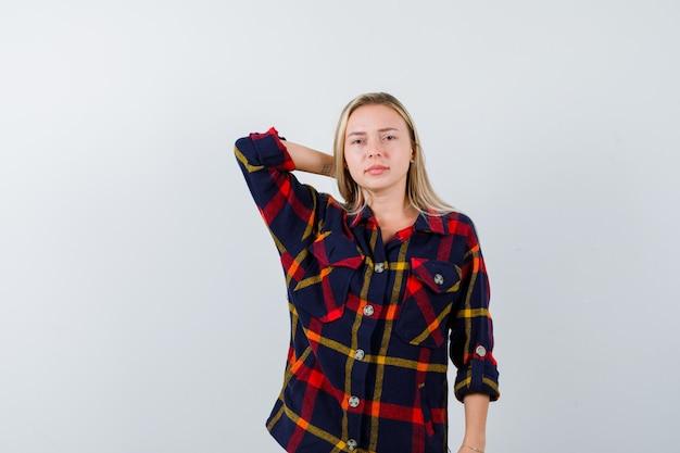 Jovem senhora de camisa, segurando a mão atrás da cabeça e olhando confiante, vista frontal.