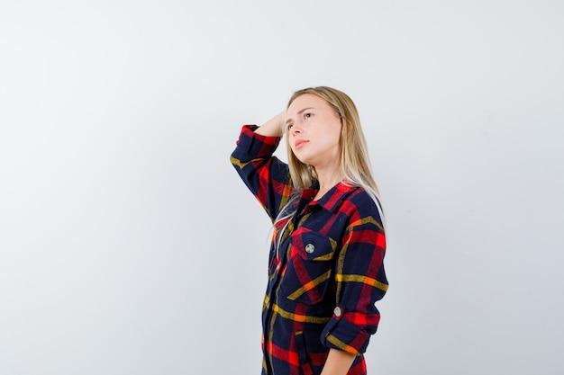 Jovem senhora de camisa, segurando a mão na cabeça e olhando pensativa, vista frontal.