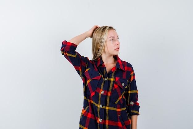 Jovem senhora de camisa, segurando a mão na cabeça enquanto olha para longe e parece pensativa, vista frontal.