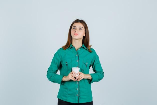 Jovem senhora de camisa, segurando o copo plástico de café e olhando pensativa, vista frontal.
