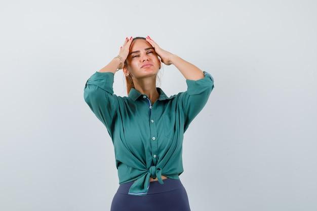 Jovem senhora de camisa verde com as mãos na cabeça e parecendo cansada, vista frontal.
