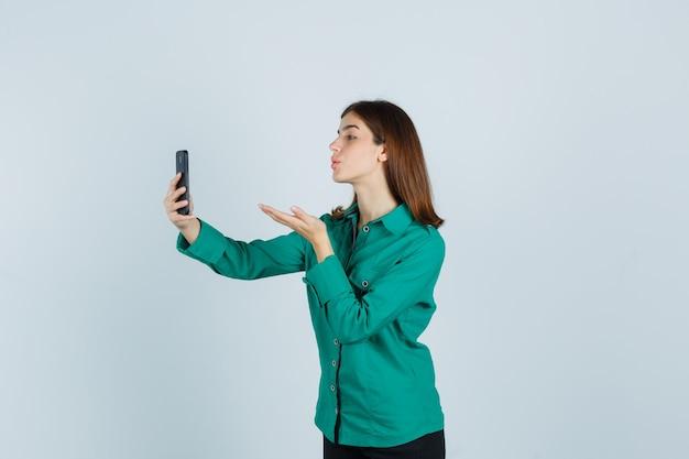 Jovem senhora de camisa verde enviando beijo no ar enquanto toma selfie no smartphone e parece vista frontal em paz.